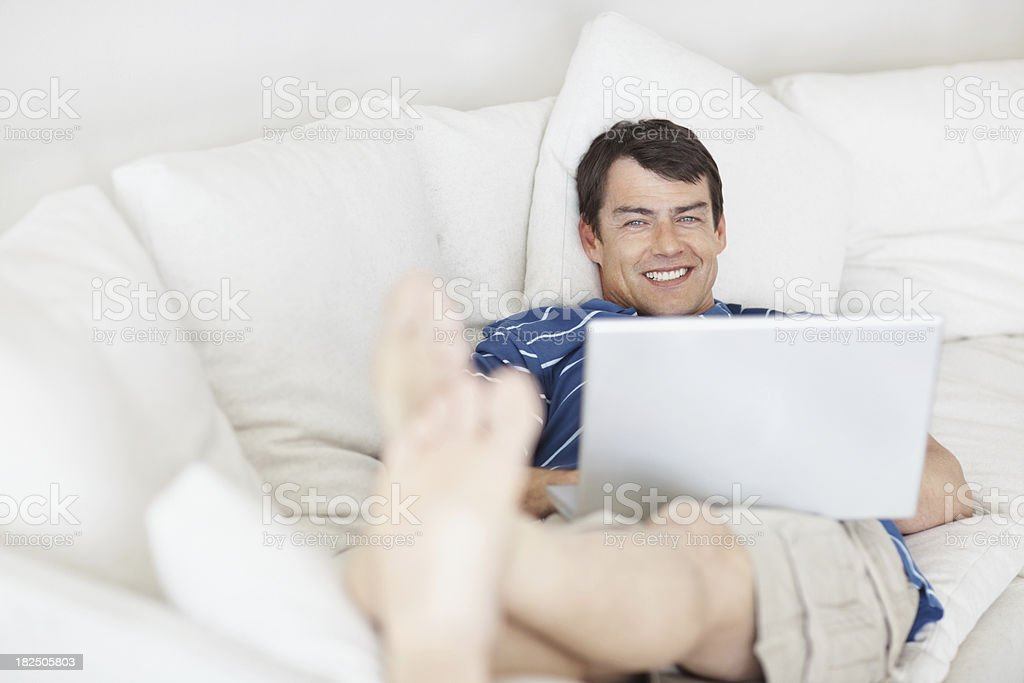 Smiling guy relaxing on the couch with a laptop royalty-free stock photo