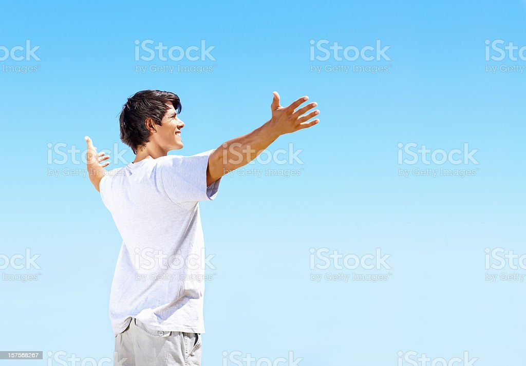 Smiling guy with arms outstretched against blue sky royalty-free stock photo