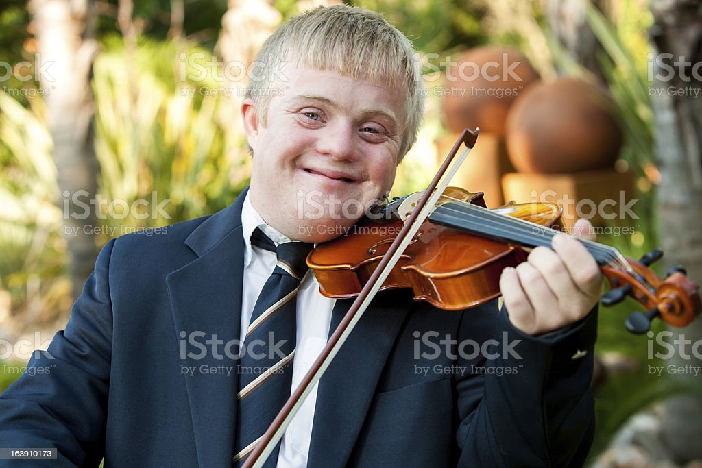 Souriant garçon jouant le violon pour personnes à mobilité réduite. photo libre de droits