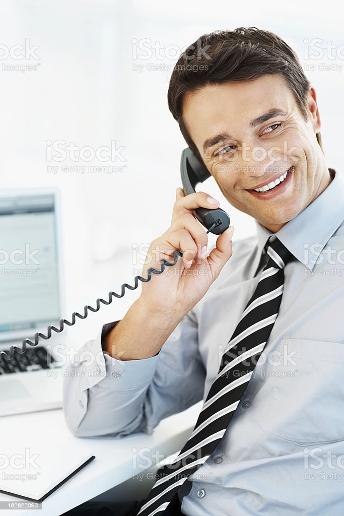 Smiling handsome businessman talking on the phone in office royalty-free stock photo