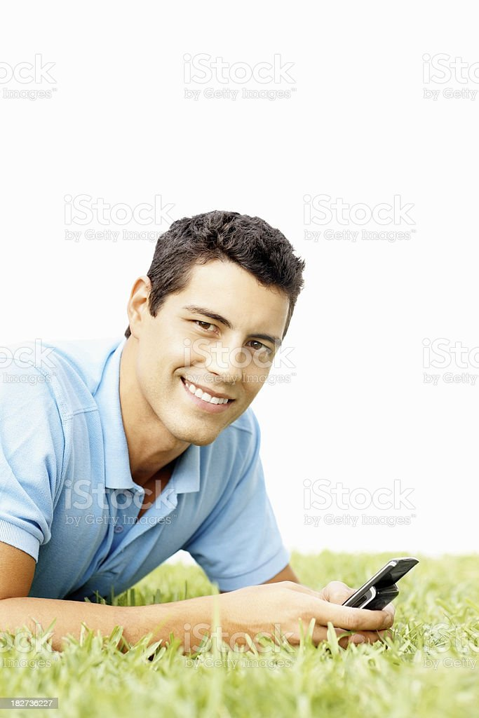 Smiling handsome guy using a cellphone on grass royalty-free stock photo