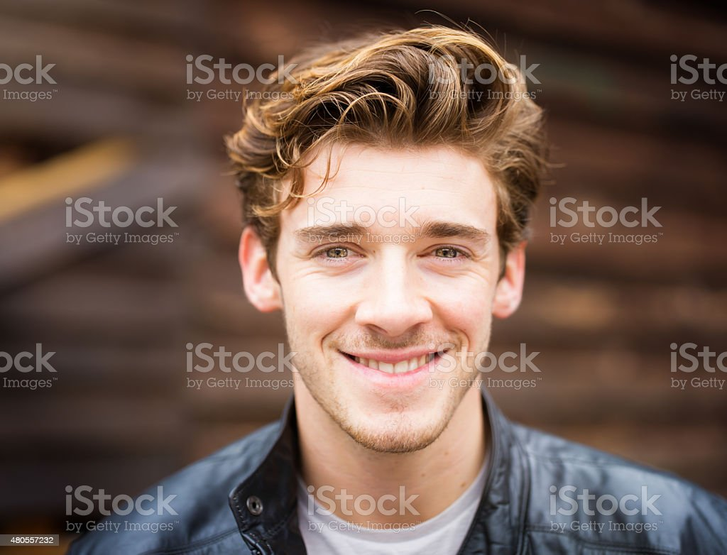 Smiling handsome happy cheerful English male student wearing leather jacket stock photo