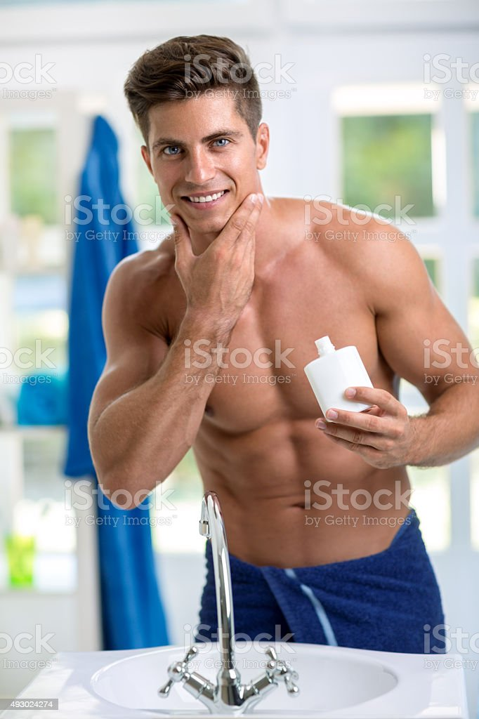 Smiling handsome  man applying after shave stock photo