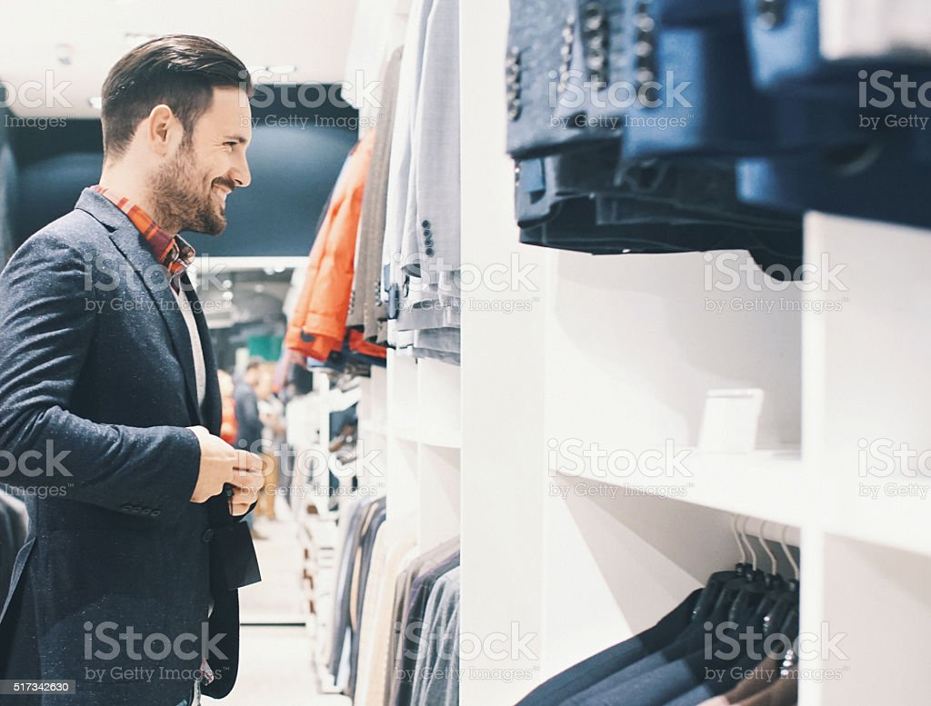 Smiling handsome man buying clothes. stock photo