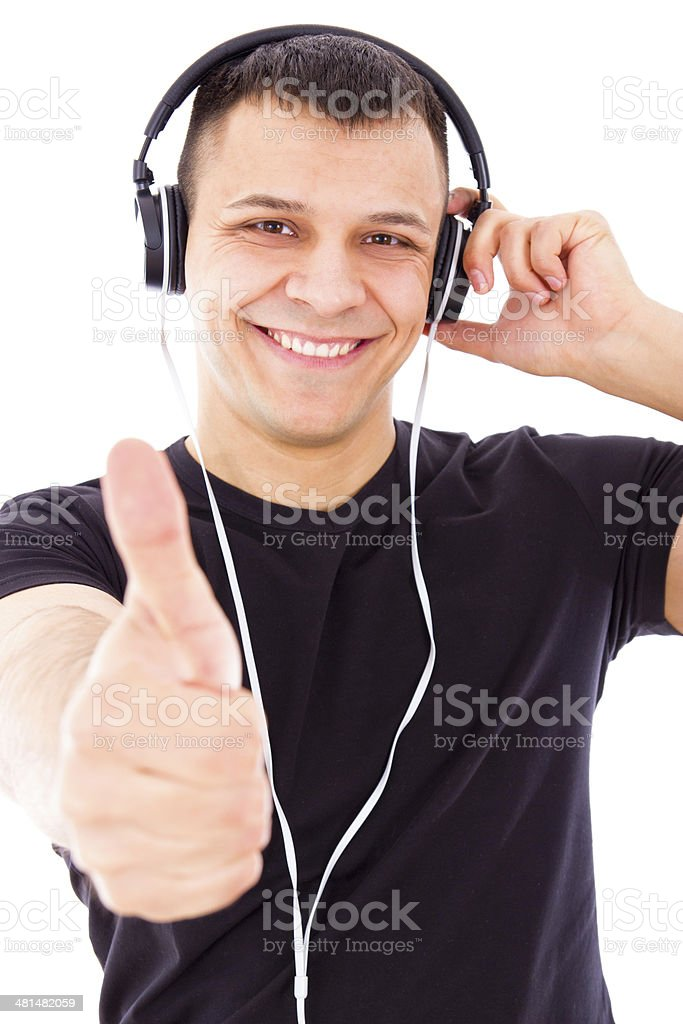 smiling handsome man listening to music showing thumbs up stock photo