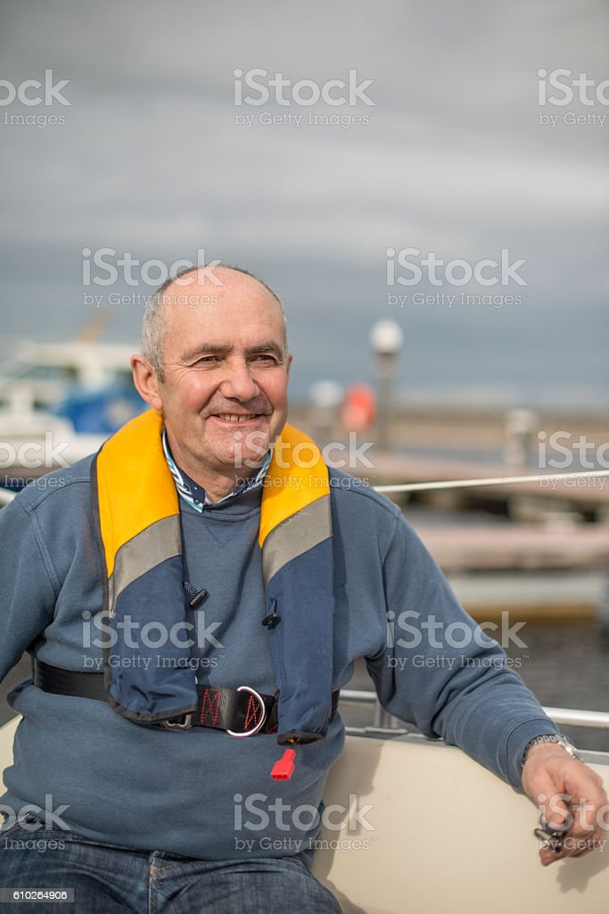 Smiling handsome man on his sail boat stock photo