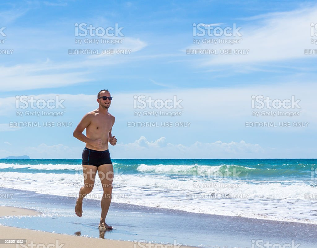 Smiling Handsome Man Power Walking Fitness Exercise Beach Thailand stock photo