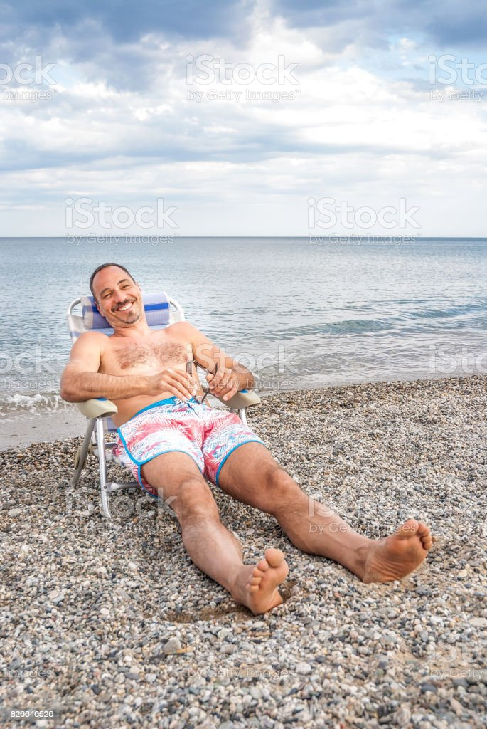 Smiling Handsome Man Sunbathing On His Deck Chair stock photo