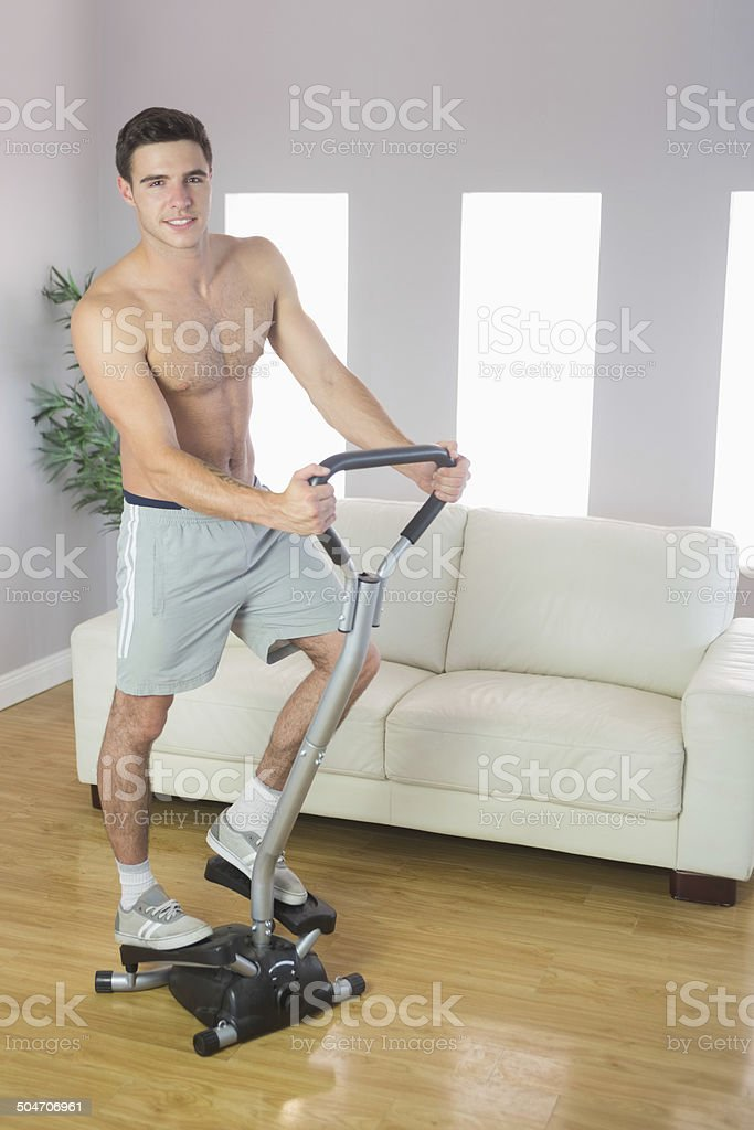Smiling handsome man training on stair climber stock photo