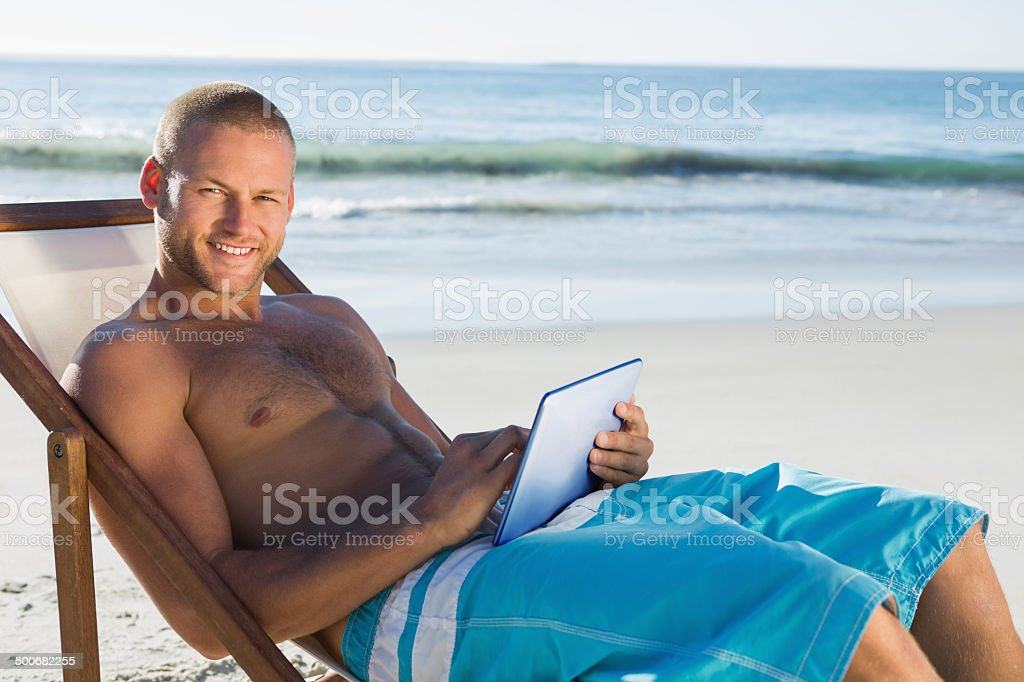 Smiling handsome man using his tablet while sunbathing stock photo
