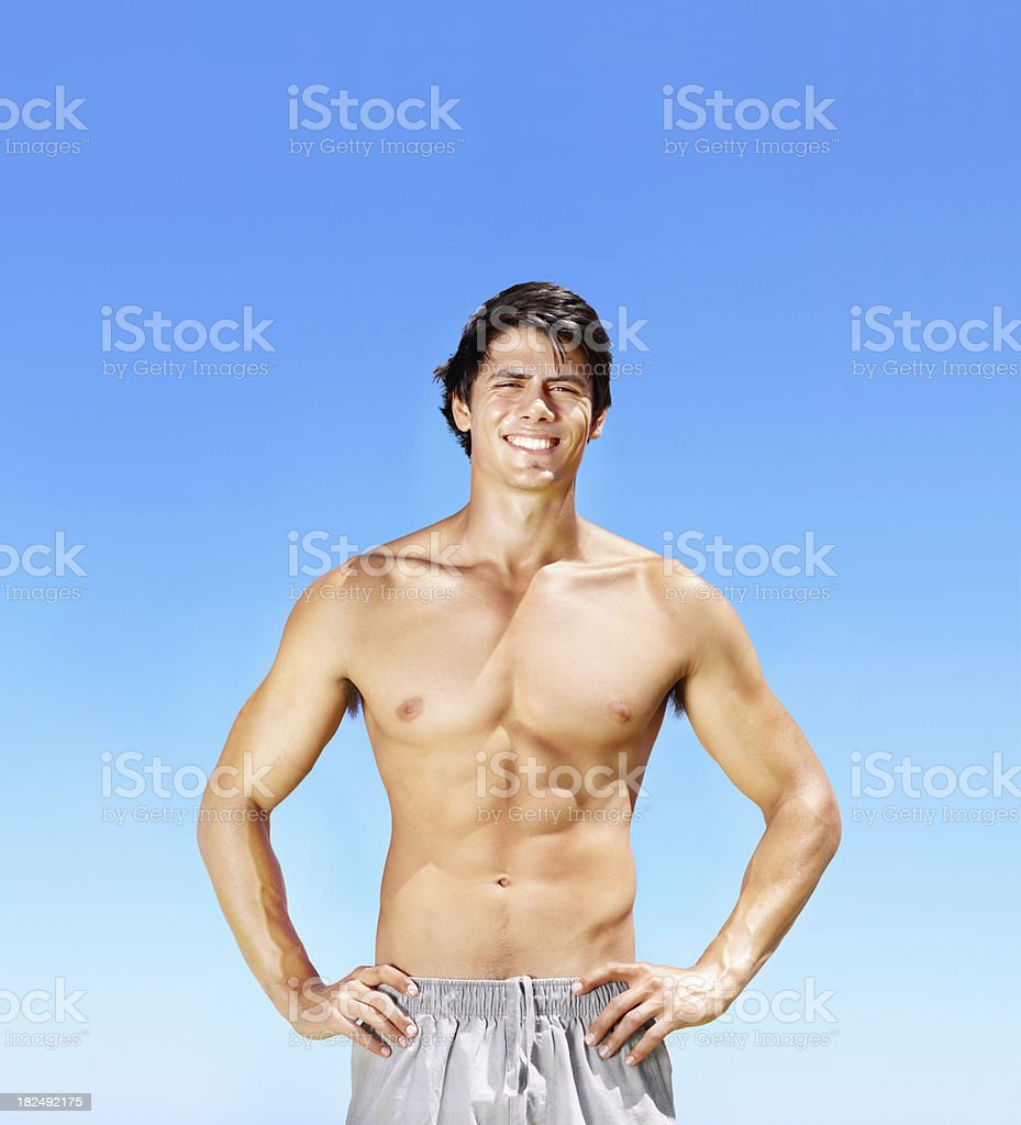 Smiling handsome muscular guy standing against blue sky royalty-free stock photo