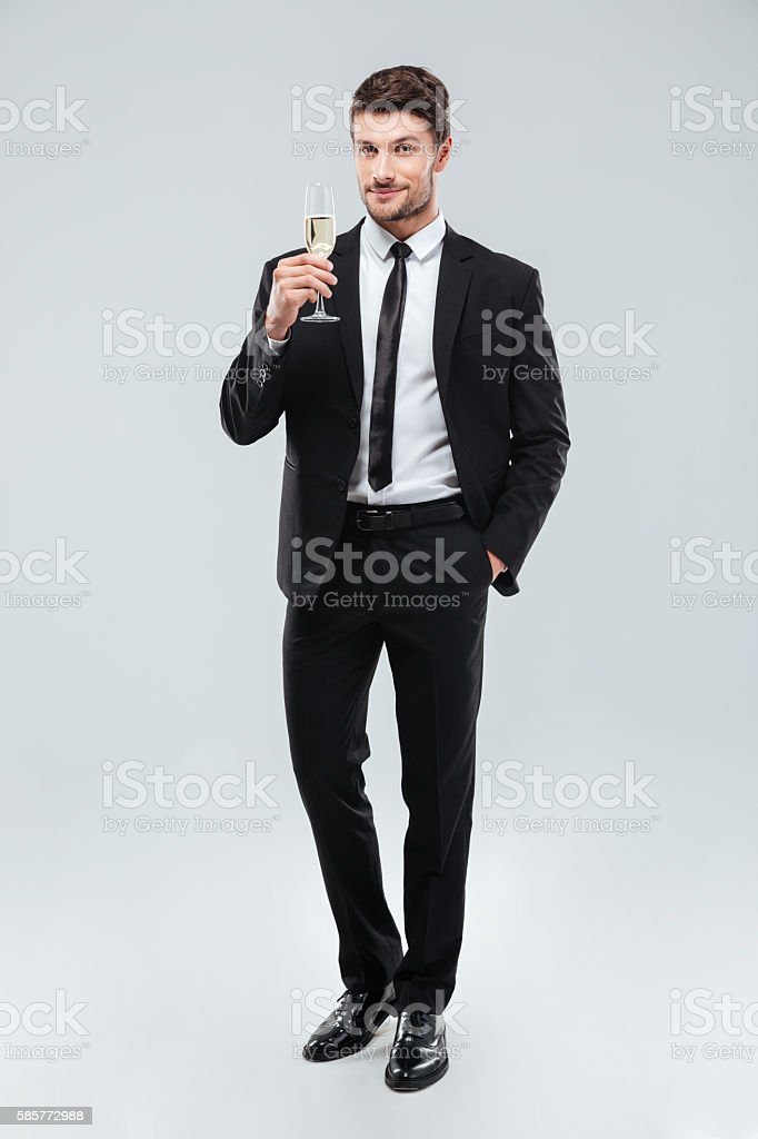 Smiling handsome young businessman standing and holding glass of champagne stock photo