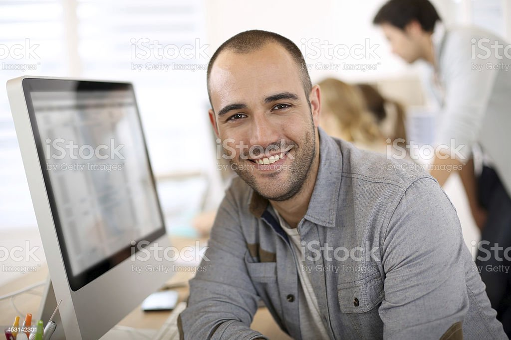 Smiling handsome young man in office stock photo
