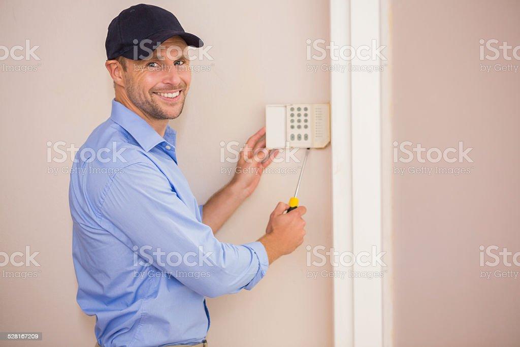 Smiling handyman fixing an alarm system stock photo