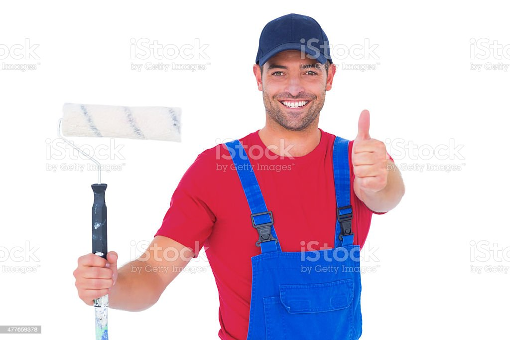 Smiling handyman with paint roller gesturing thumbs up stock photo