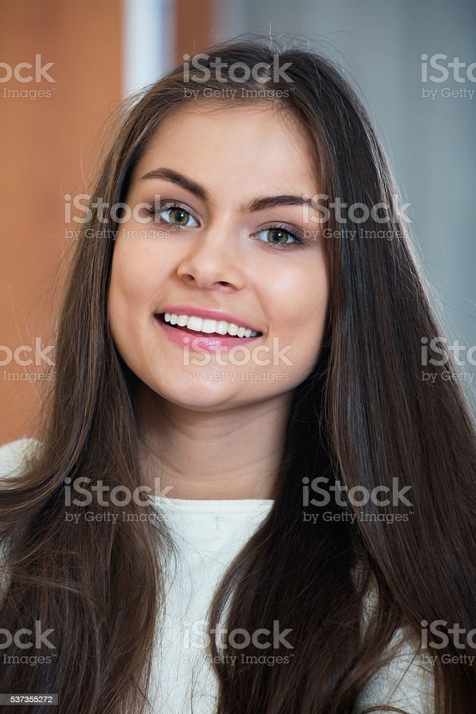 Smiling happy  adult girl in white sweater stock photo