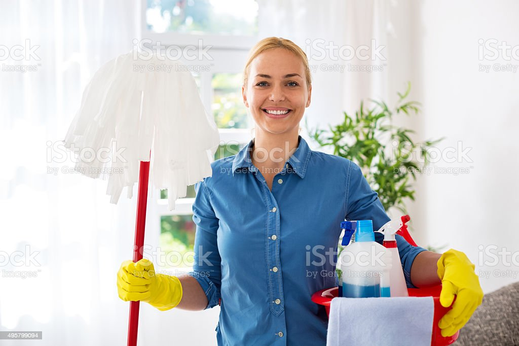 Smiling happy attractive housewife ready for cleaning home stock photo