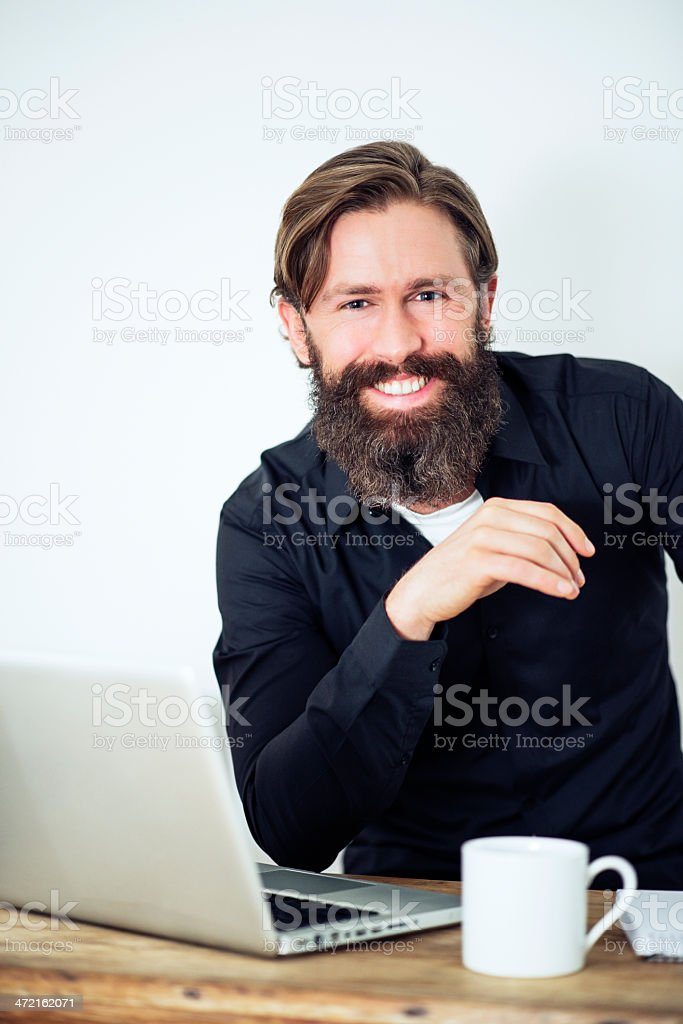 Smiling Happy bearded Man working at desk royalty-free stock photo