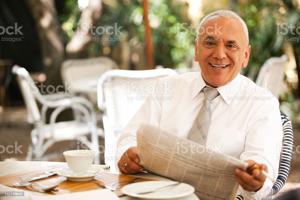 Smiling happy businessman enjoying his morning breakfast and fresh newspaper. royalty-free stock photo