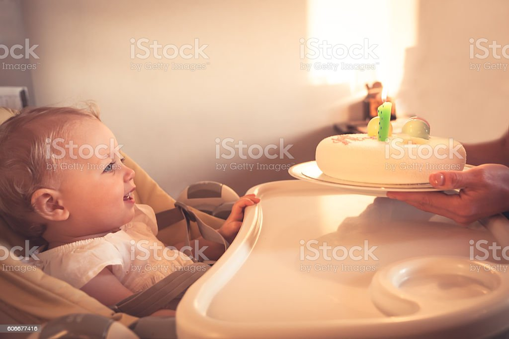 Smiling happy child looking at birthday cake with burning candle stock photo