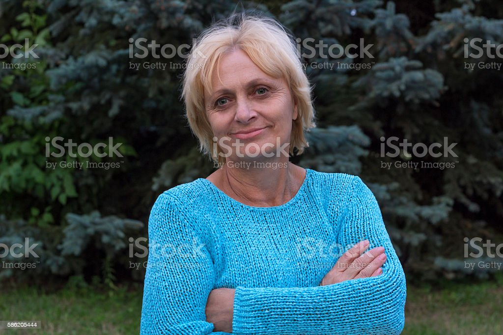 Smiling happy ellderly woman stands with crossed arms stock photo