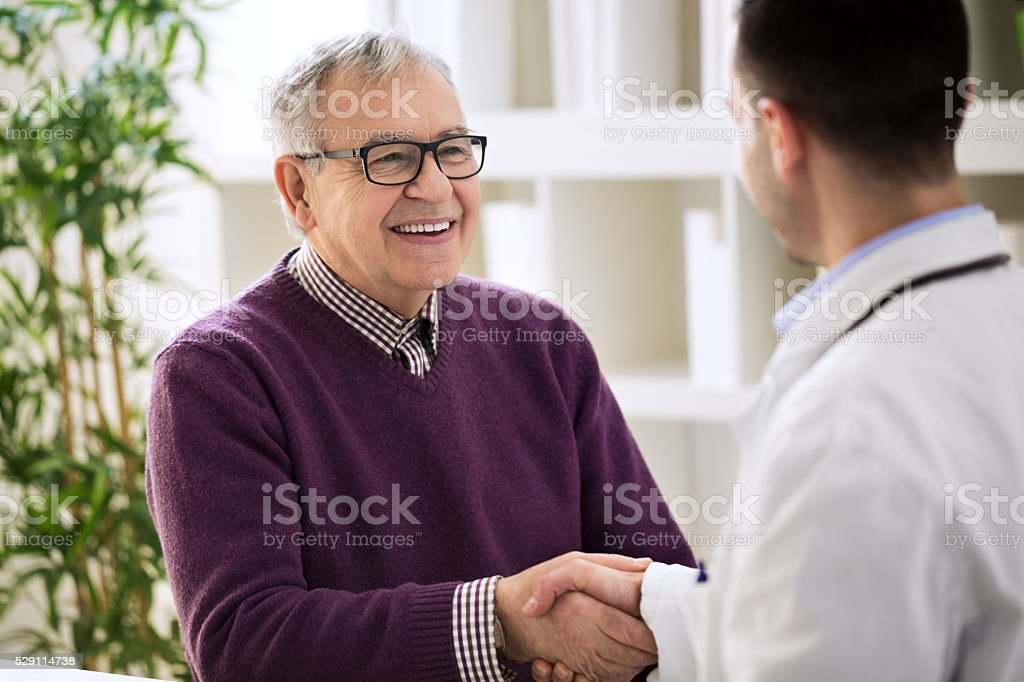 Smiling happy healthy old male shaking with doctor stock photo