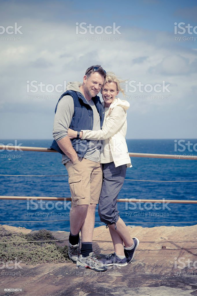 Smiling, happy mature adult couple embracing on coastal cliff stock photo