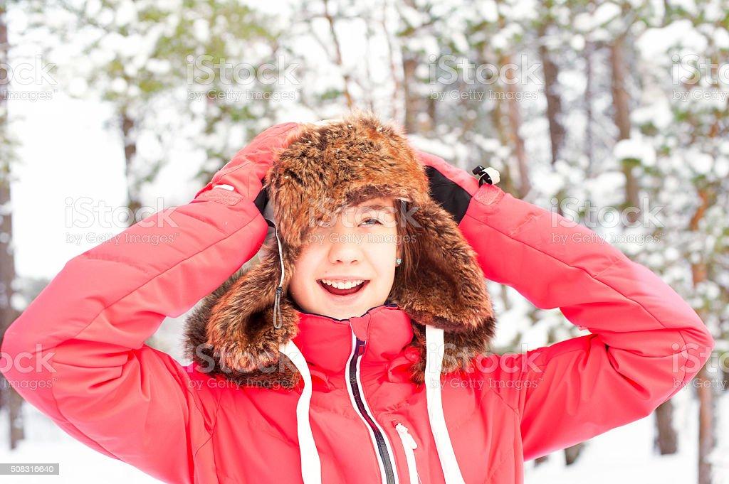 Smiling happy teenage girl in warm earflap having fun stock photo
