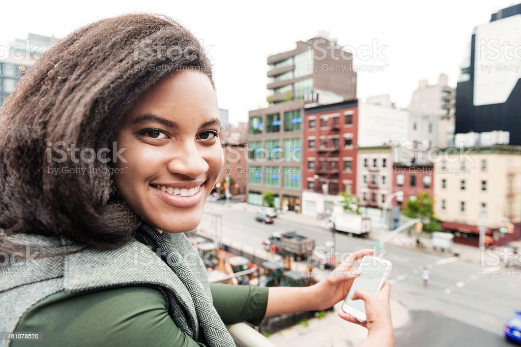 Smiling Happy Urban NYC Woman with Phone Above City Buildings stock photo