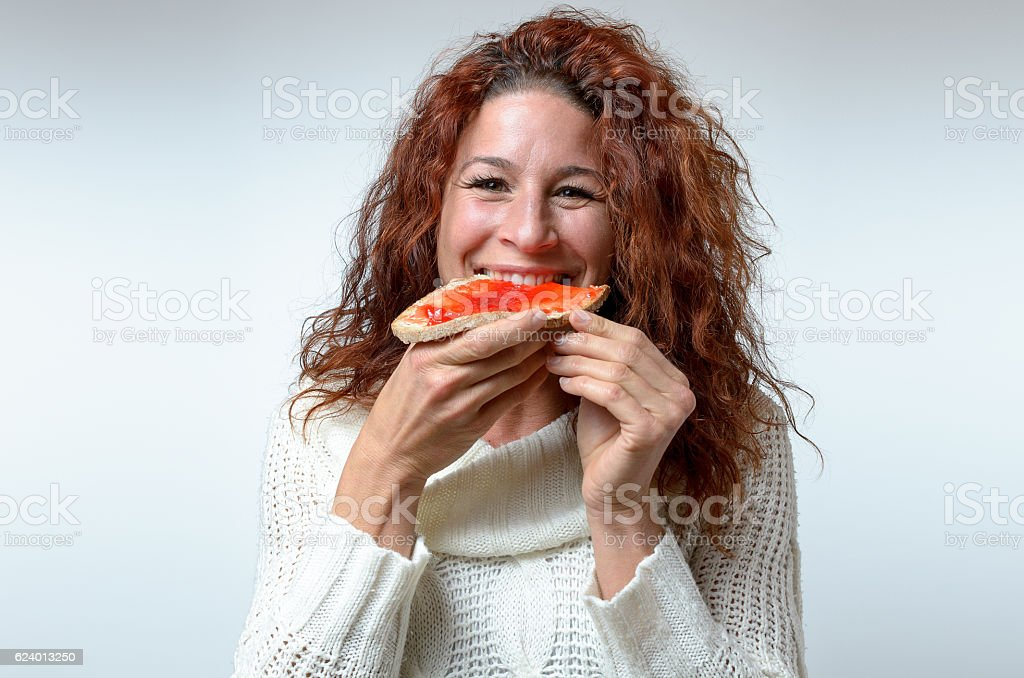 Smiling happy woman biting into jam on bread stock photo