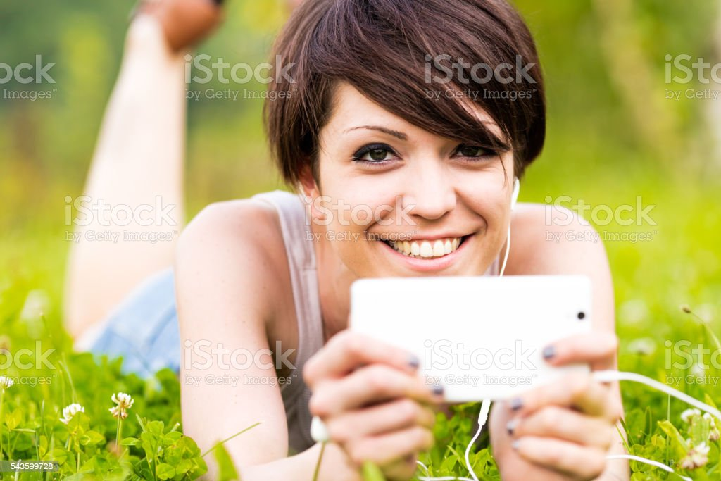 Smiling happy woman listening to music outdoors stock photo