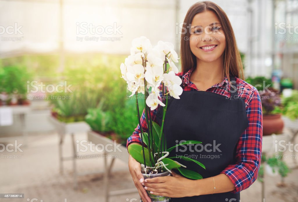Smiling happy young florist in her nursery stock photo
