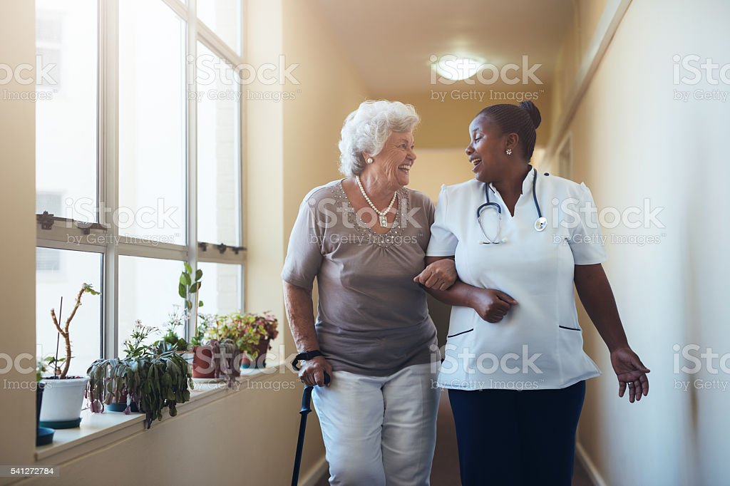 Smiling healthcare worker and senior woman walking together stock photo