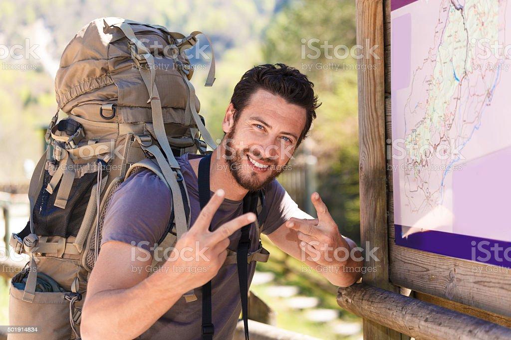 Smiling hiker doing the V sign stock photo