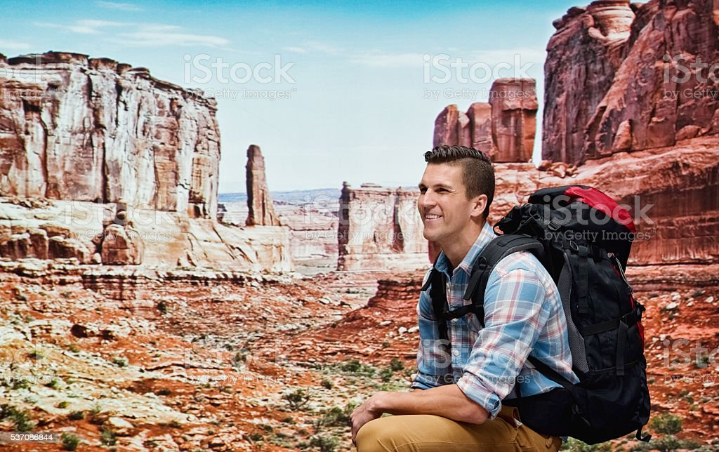 Smiling hiker sitting in mountain stock photo