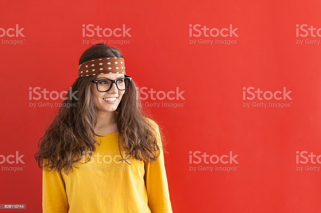 Smiling hippie woman on red background stock photo