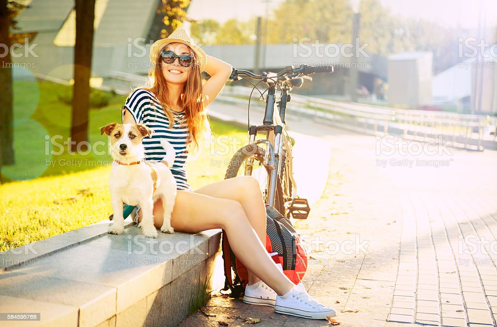 Smiling Hipster Girl with her Dog in Summer City stock photo