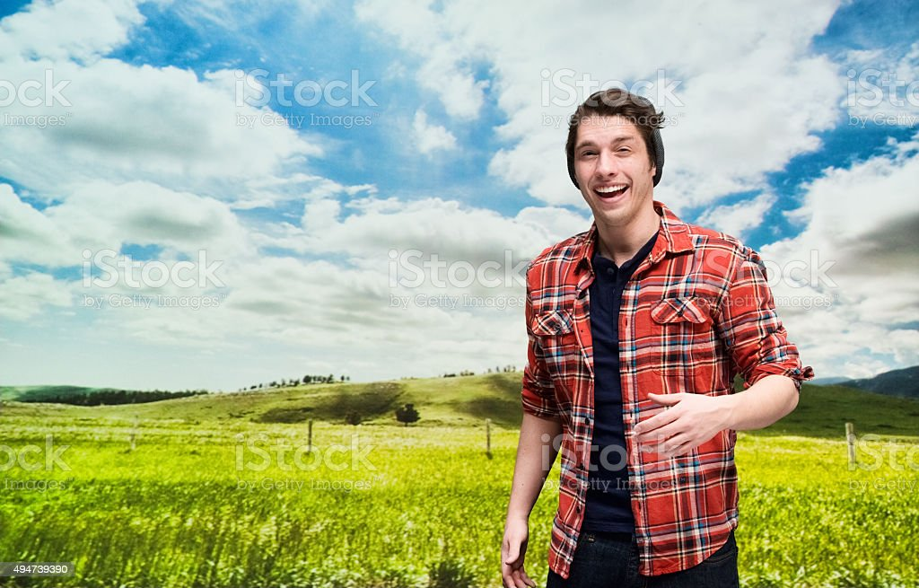 Smiling hipster in front of rural scene stock photo