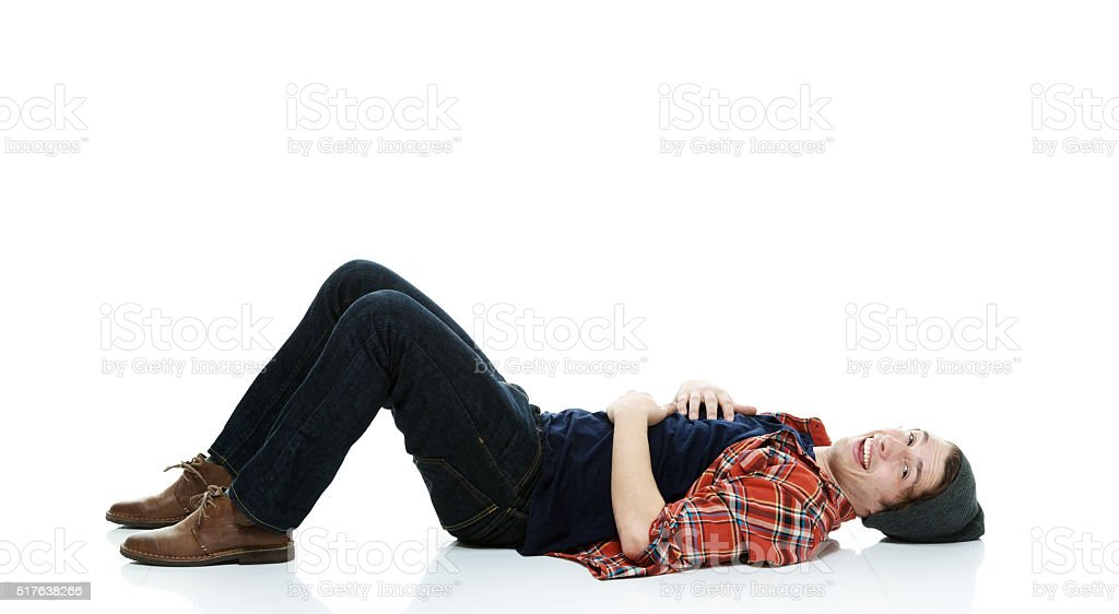 Smiling hipster lying on floor stock photo