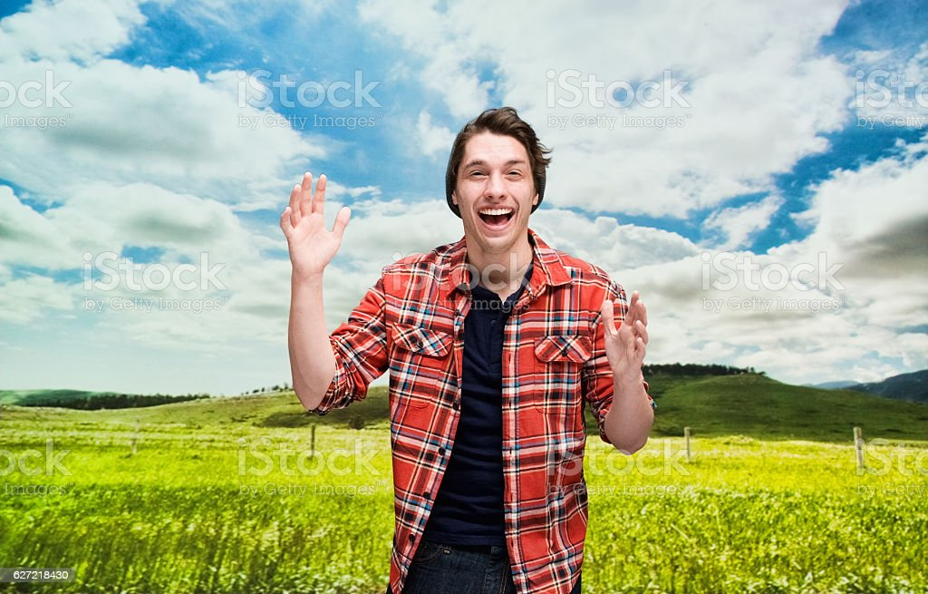 Smiling hipster standing in front of rural scene stock photo