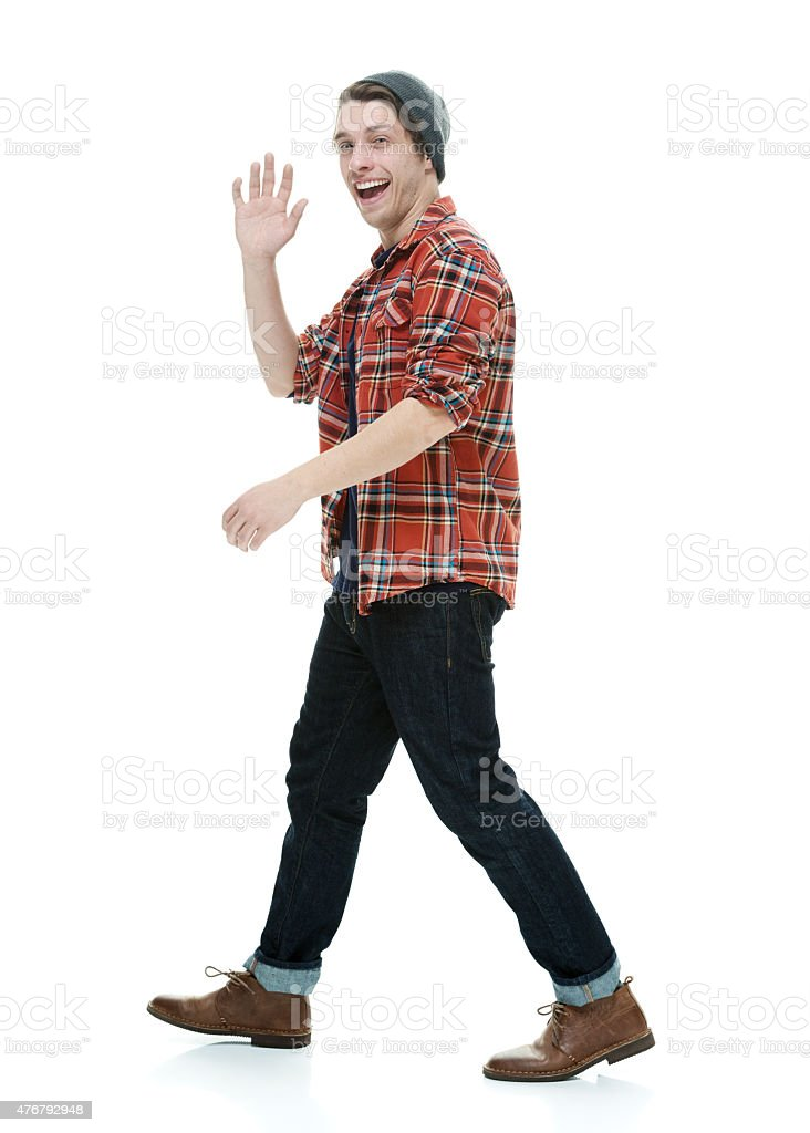 Smiling hipster walking and waving hand stock photo