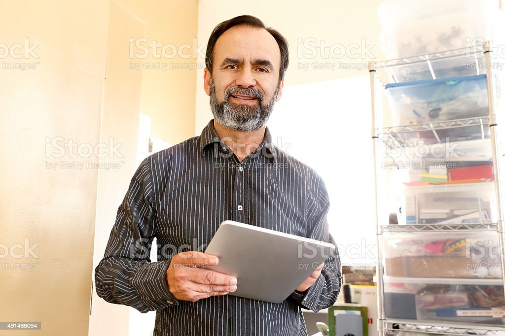 Smiling Hispanic Businessman Looking At Camera Holding Digital Tablet stock photo