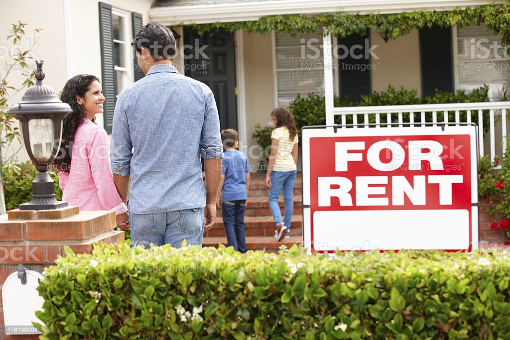 Smiling Hispanic family outside rental home stock photo