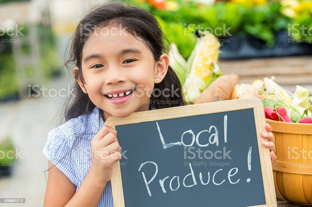 Smiling Hispanic Girl at farmers market stock photo