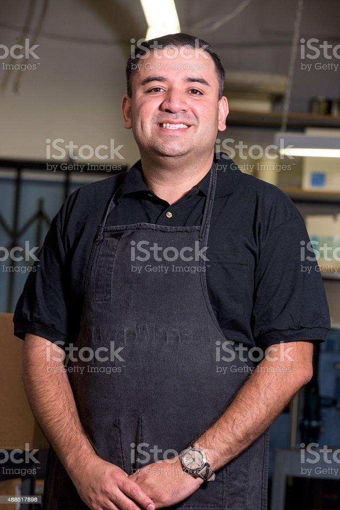 Smiling hispanic man posing at his workplace stock photo