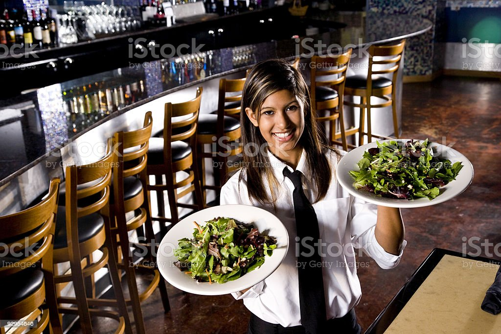 Smiling hispanic waitress serving salads stock photo