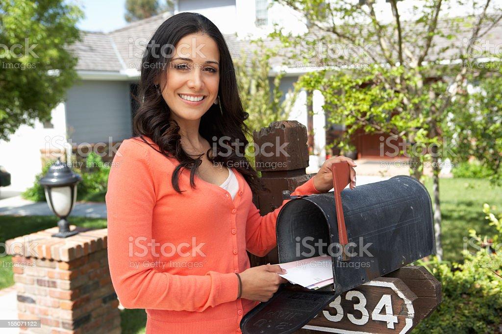 Smiling Hispanic woman checking mailbox at home stock photo