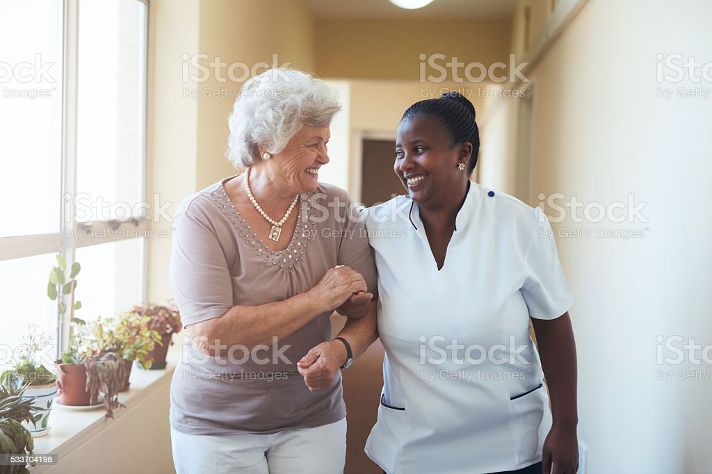 Smiling home caregiver and senior woman walking together stock photo