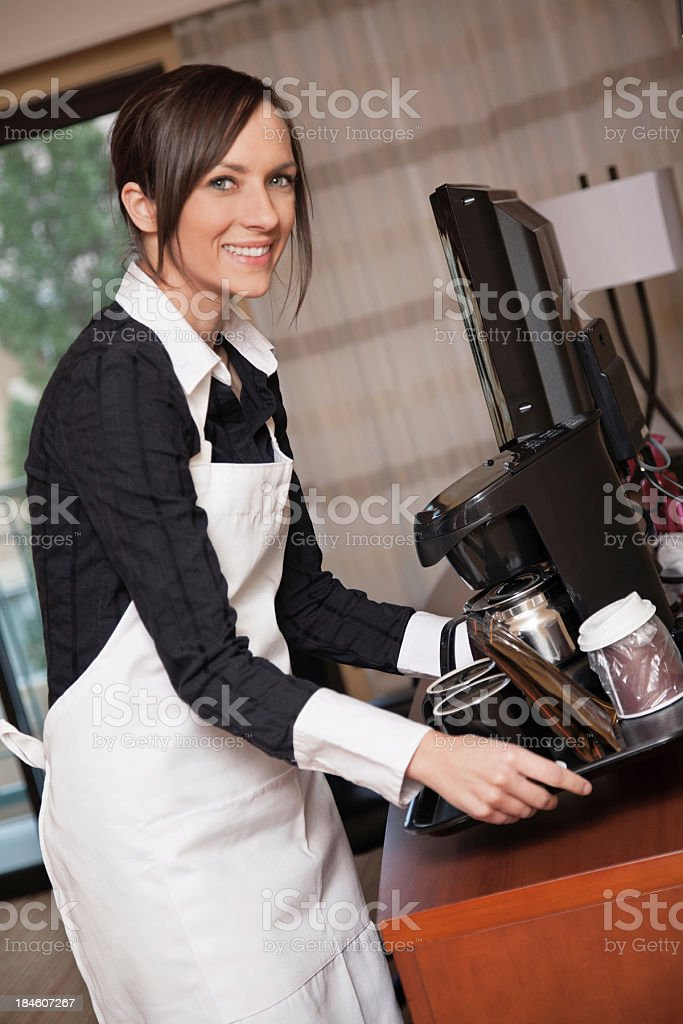 Smiling hotel maid setting up coffee and condiments in room royalty-free stock photo