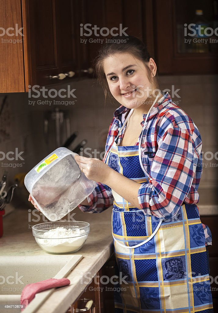 smiling housewife interspersing flour from bowl royalty-free stock photo